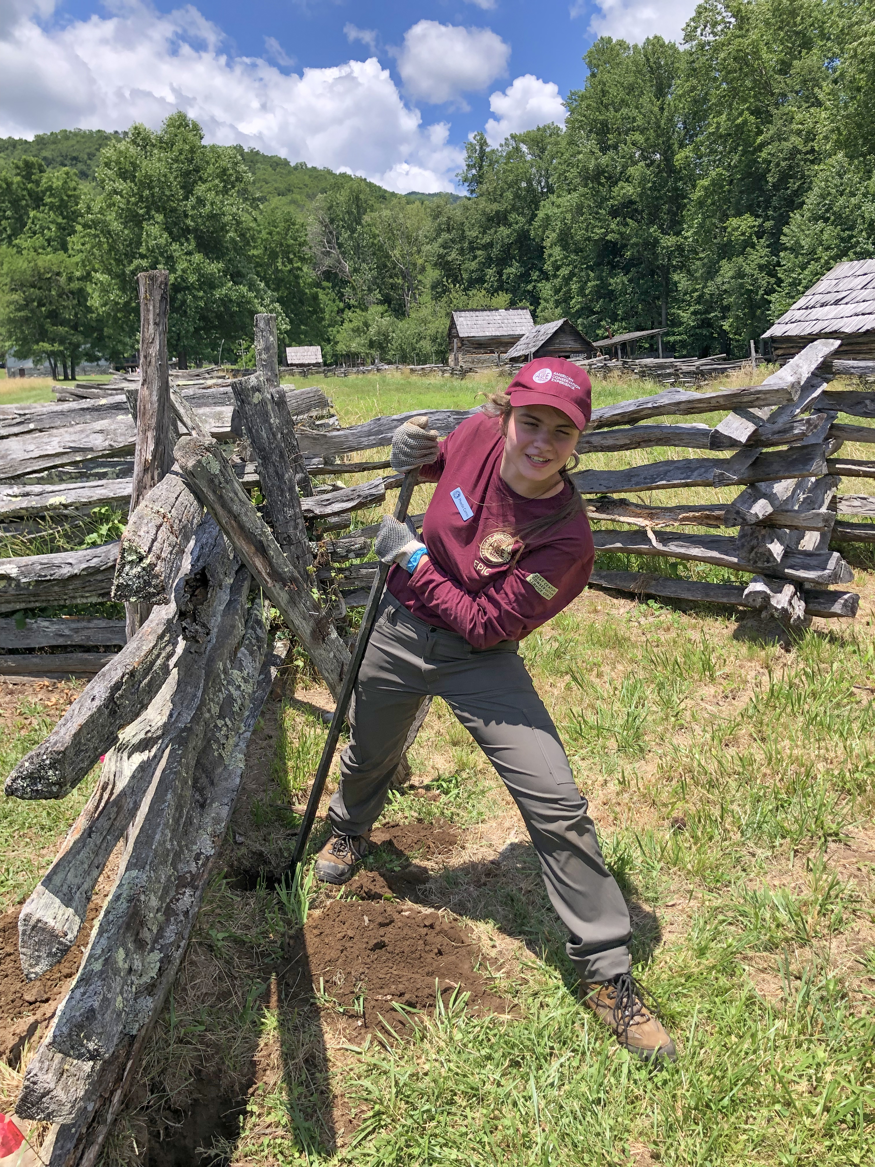 Great Smoky Mountains National Park summer intern Phoebe Carnes of Whittier, NC, struggles to loosen a large underground rock with a pry bar while repairing a fence at the Oconaluftee Visitor Center. Courtesy NPS.