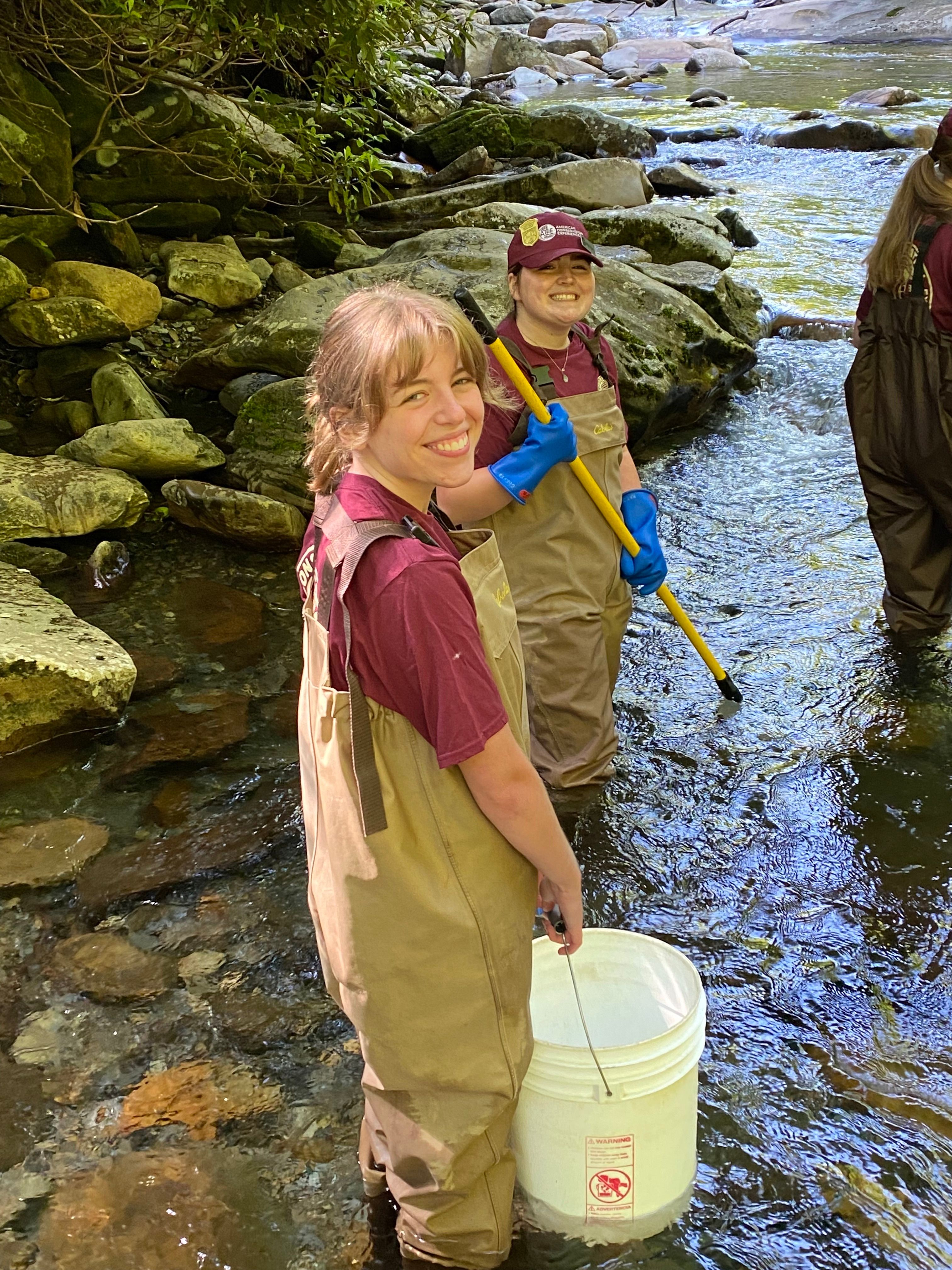 Great Smoky Mountains National Park interns Kaylie Hallcox and Morgan Kirkpatrick spent time monitoring fish populations this summer. They were supporting fisheries technicians who had stunned the fish, following them with nets and buckets to collect fish for identification, counting, weighing, and measuring. Image courtesy of NPS.